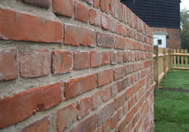 Reclaimed red european sized bricks for this new wall made to look old in a rural part of Kent.